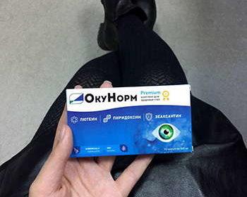 Девушка демонстрирует препарат Окунорм для зрения